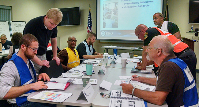 Alex McCarthy, director of the Tuscarawas County Homeland Security and Emergency Management Agency, interacting with health officials and first responders during an exercise.
