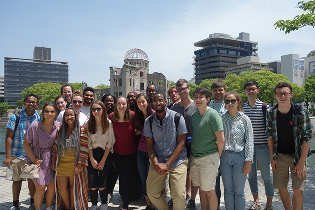 A group of students stand before the Hiroshima Peace Memorial, a building that withstood the atomic bombing of Hiroshima and is now preserved as a memorial the tens of thousands who lost their lives in the attack.