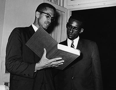 Malcolm X reading the Quran