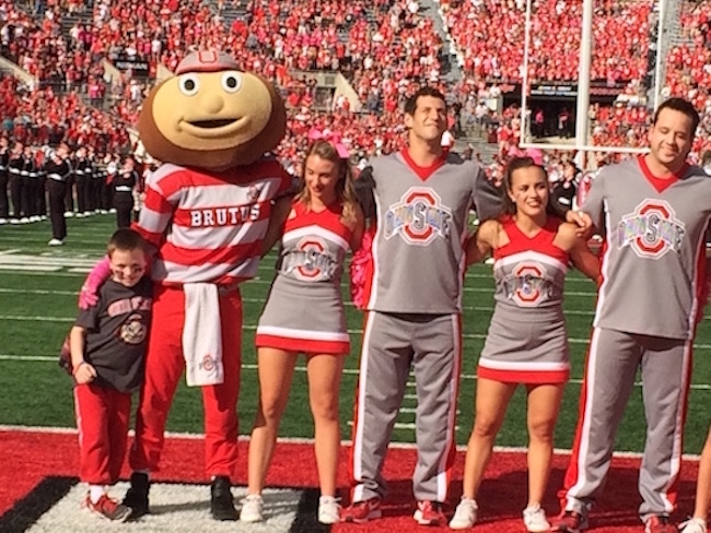 Evan stands with Brutus and the cheer team during Carmen Ohio