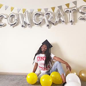 "Dube poses under ""Congrats"" balloons"