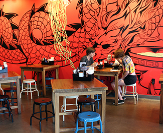 Patrons sit in front of a dragon mural inside Fukuryu Ramen.