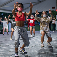 Students dance during a hip hop dance class in a specialized outdoor tent on the South Oval.