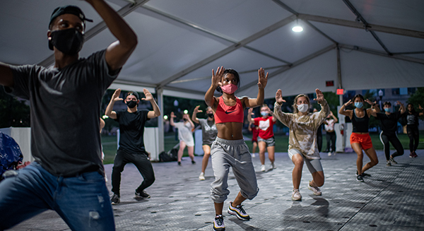 Students dance during a hip hop dance class in a specialized outdoor tent on the South Oval. Photo credit Jo McCulty.