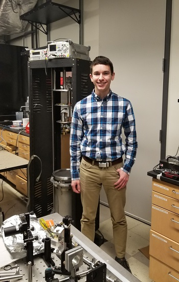 Kyle Debry stands next to a disassembled low temperature cryostat for single-photon detectors. Located in the Physics Research Building, this is currently the main tool for his research.
