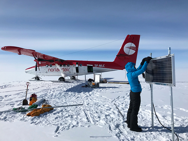 Michalea King, Earth sciences graduate student, checks on an instrument her team installed on the Greenland Ice Sheet.
