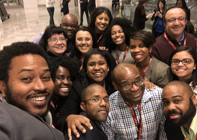 Trevon Logan poses with mentees of the AEA Mentoring Program.