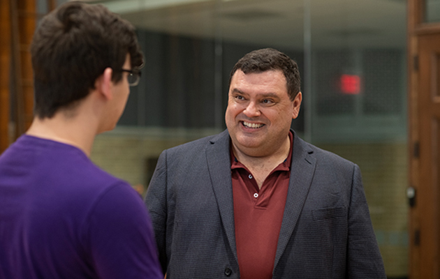 Michael Neblo, professor of political science, chats with a student at an event in 2019. Photo credit Jo McCulty.