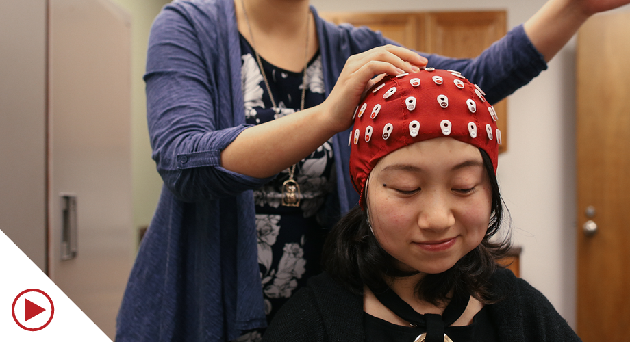 Student getting fitted in cap for an experiment
