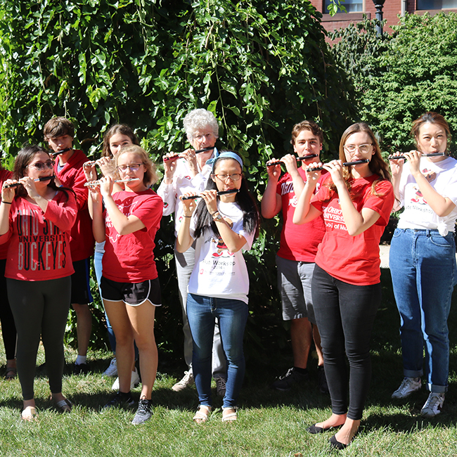 Jones and current School of Music students practice their piccolo performance in advance of marching with The Ohio State University Marching Band on Oct. 5