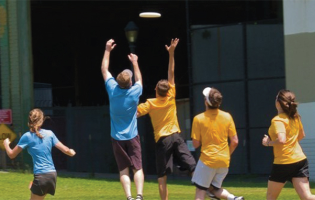 Young adults playing frisbee.