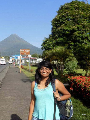 Sreelakshmi Suresh standing in front of Volcán Arenal in Costa Rica.