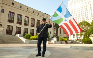 Professor of design Paul Nini waves The People's Flag of Columbus in front of Columbus City Hall. Photo courtesy of Brian Kaiser.