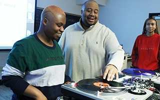 Jason Rawls demonstrates how to scratch on a record for a student