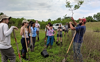 Ohio State students learn about saplings they are about to plant during a field school in southern Louisiana. Photo credit: Mary Thomas