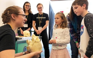 Members of APOP speak with children at COSI