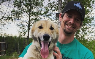 Matthew Failor poses with one of his sled dogs