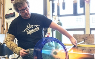 Jonathan Capps, a glassmaker in the Department of Art, uses a blowtorch on a piece of glass art he's making. Capps will spend nine months in Finland for a Fulbright-funded research project.
