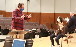 Jae Park conducts during rehearsal.